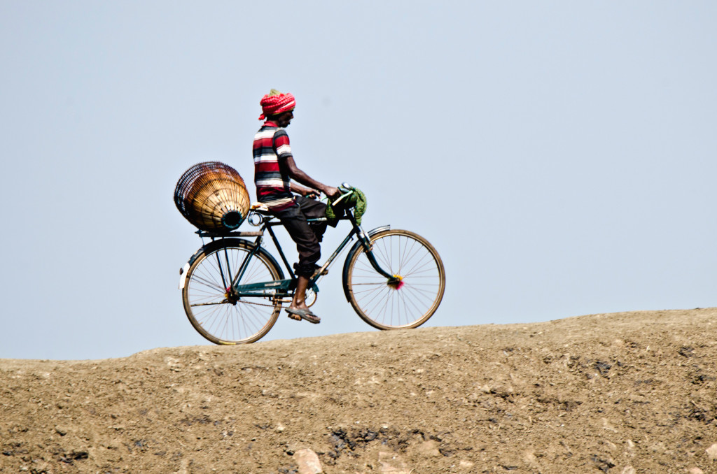 Cyclist carrying locally made fish trap